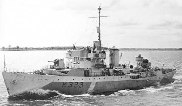 Une photo en noir et blanc d'un navire de guerre de type corvette, avec l'inscription K333, naviguant au large en direction de la rive.