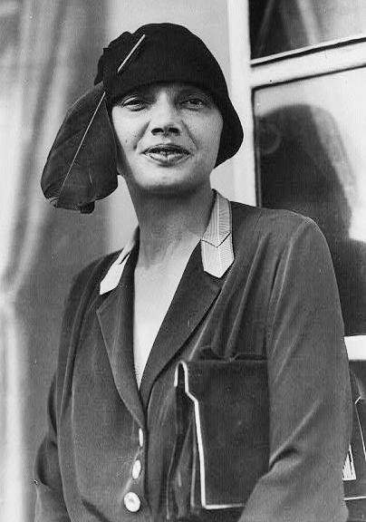 Une photo en noir et blanc d'une femme aux lèvres charnues qui regarde directement l'appareil-photo. Elle porte un sac à main sous le bras et un chapeau en forme de bol avec une grosse plume.