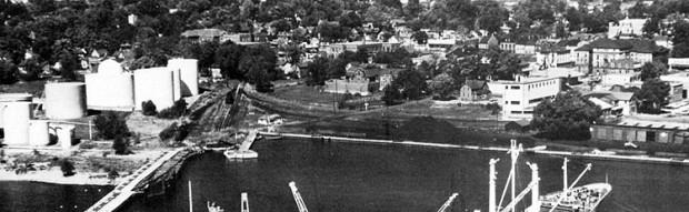 Une photo en noir et blanc du port industriel avec des réservoirs à pétrole blancs à gauche, des lignes de chemin de fer et des tas de charbon au centre ainsi qu'un wagon couvert à droite. Le Victoria Hall se trouve au loin à droite.
