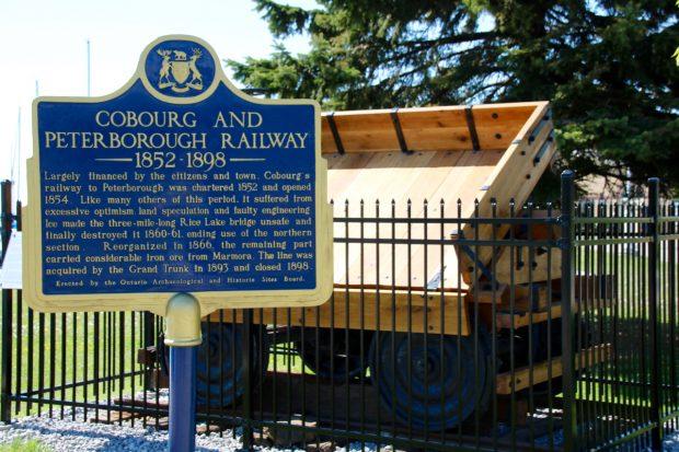 plaque commémorative bleue de la province de l'Ontario relatant l'histoire de la Cobourg and Peterborough Railway. La plaque est installée devant une réplique grandeur nature d'un wagon de minerai près de l'endroit où l'original fut construit en 1867.