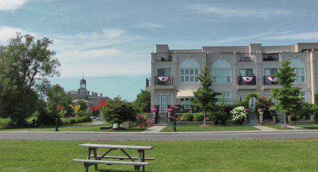 Une table à pique-nique sur une pelouse verte en face d'un immeuble à condominiums de deux étages. Au loin, il y a un grand édifice avec une coupole.