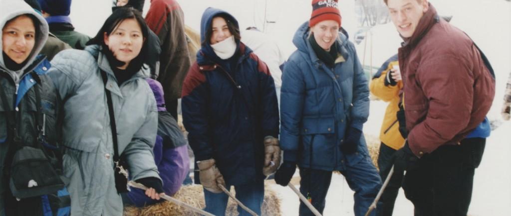 Plusieurs jeunes habillés en vêtements d'hiver qui font griller du pain bannock sur un feu. L'activité faisait partie du festival des trappeurs de 1999.