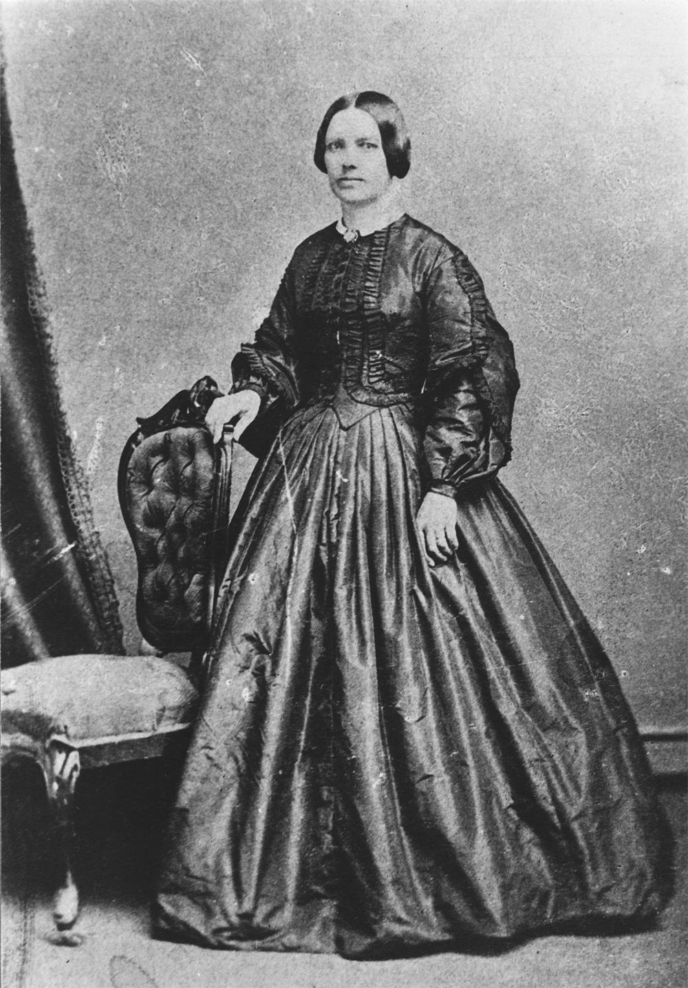 Photo de Lady Strathcona (Isabella Sophia Hardisty) debout près d'une chaise, en tenue de soirée