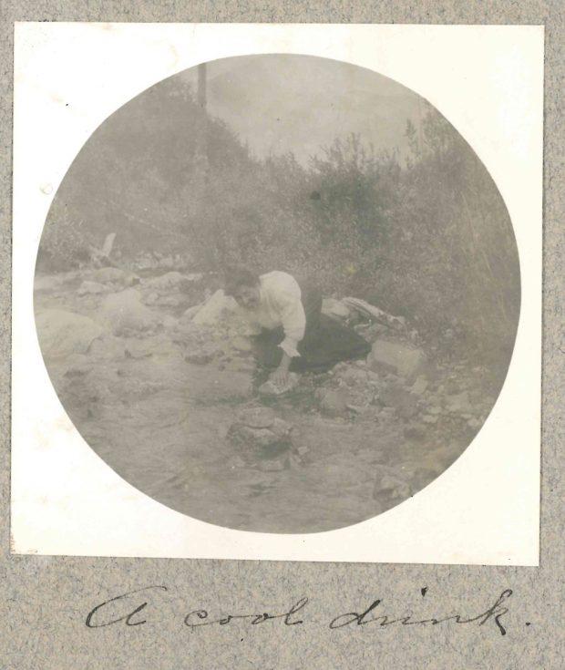 Photo d'une femme au bord d'un ruisseau prenant de l'eau