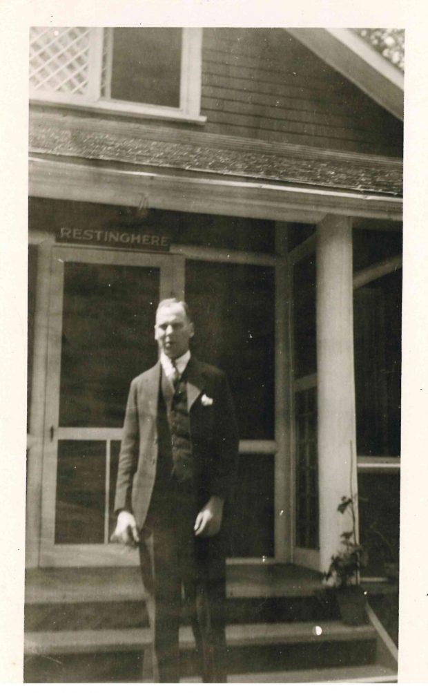 Photo d'une personne devant le chalet de la famille Lougheed à Banff (avec le nom du chalet, « Restinghere » au-dessus de la porte)