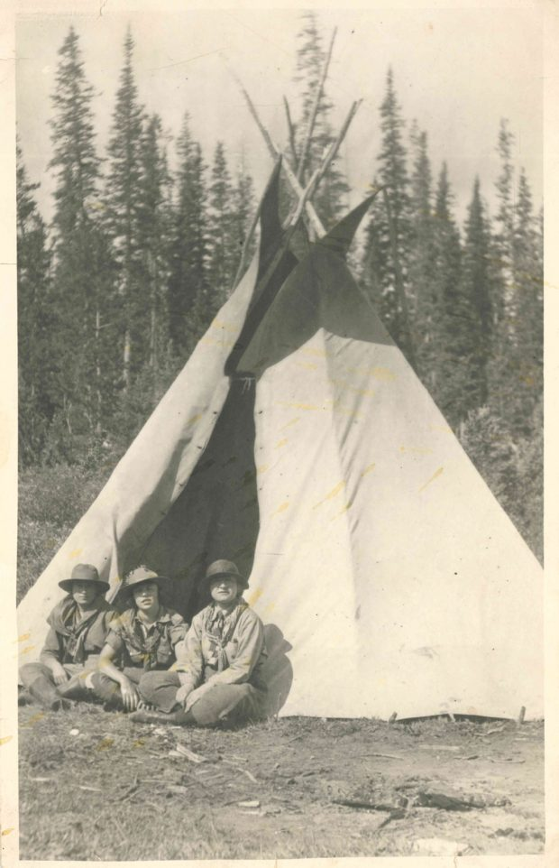 Photo de Dorothy Lougheed entre deux autres filles habillées en éclaireuses, devant un tipi