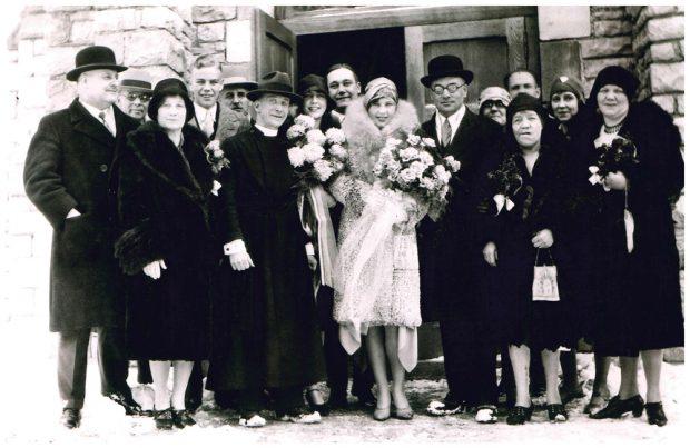 Photo de groupe du mariage de Clarence Lougheed devant une porte d'église à Banff, Isabella dans la première rangée, à côté de Clarence