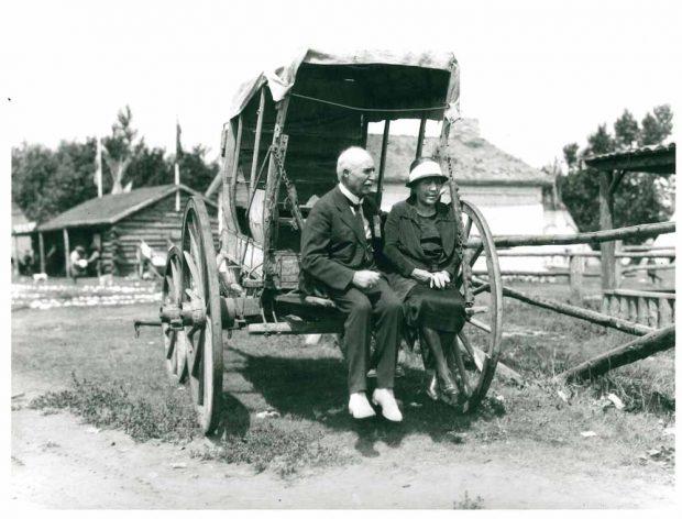 Belle et J.J. McHugh assis en arrière d'un vieux chariot couvert au Stampede, en 1925