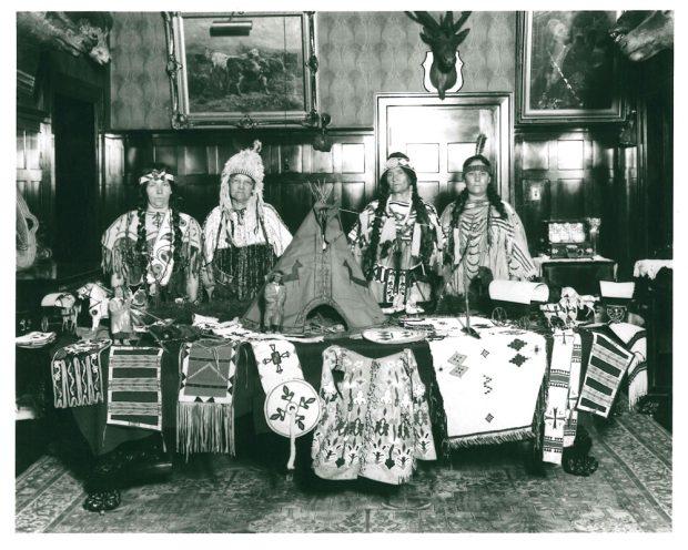 Quatre personnes portant des vêtements autochtones derrière une table avec de l'artisanat autochtone à la maison Beaulieu; groupe Southern Alberta Pioneer and Oldtimers Women, en 1923