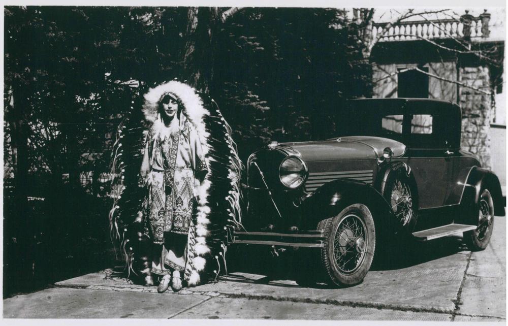 Photo de Dorothy Lougheed portant une grande coiffe de plumes à côté d'une voiture à Beaulieu