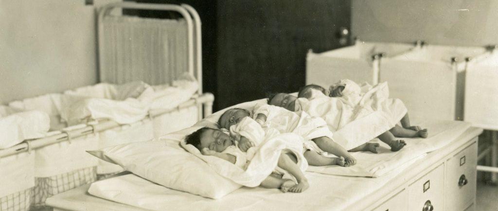 Nouveau-nés endormis alignés dans une rangée avec lits de bébé en toile de fond dans une photo en noir et blanc.