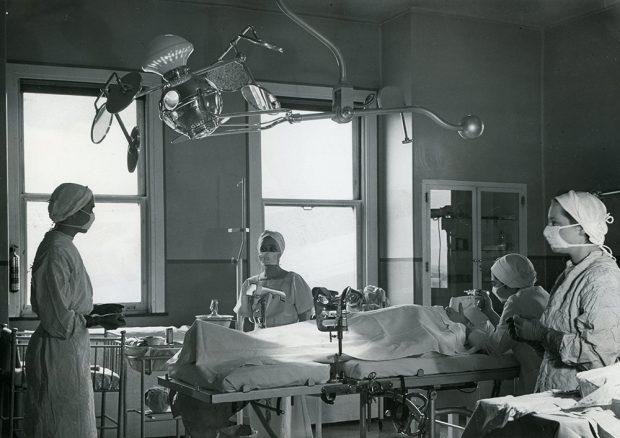 Des employées médicales se tiennent autour d'un patient sur un lit dans une salle remplie d'équipement médical dans une photo en noir et blanc.