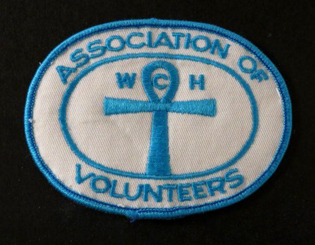 Insigne blanc avec couture bleue. Le texte dit: Association of Volunteers (Association des bénévoles)