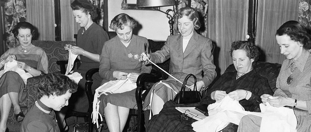 Des femmes travaillent à des œuvres de couture individuelles dans une photo en noir et blanc. Des chaises ont été ajoutées à la pièce pour les accueillir. Une femme est assise à terre dans le coin gauche.