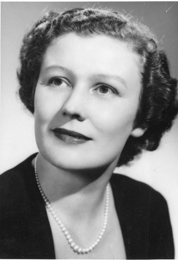 Portrait noir et blanc d'une femme souriant délicatement et portant des perles.