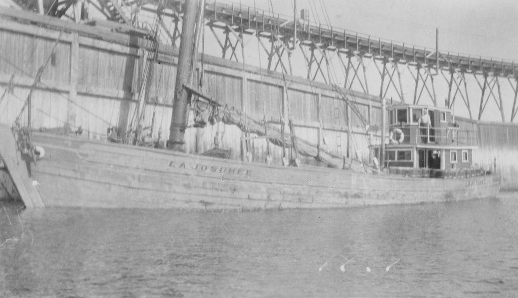 Photographie ancienne et en noir et blanc de La Josuhéee. Le bateau est en bois, la voile est baissée et on peut lire aisément le nom du bateau. À l'arrière, le capitaine Joseph Desgagnés se tient fièrement à l'extérieur de sa cabine. Au deuxième plan, on observe un quai de bois.