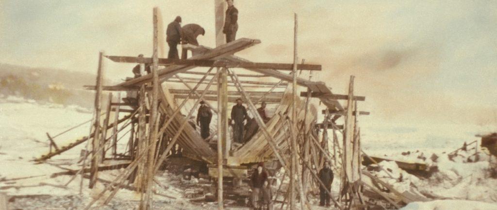 Vue d'une goélette en construction. On y voit la charpente du bateau entourée par des échafaudages. Des hommes en habits de travail se tiennent dans la cale du bateau et sur un échafaudage. Devant, se tiennent une femme, un enfant et un autre homme. La photo a été prise en hiver. On a coloré l'image, ce qui lui donne une teinte sépia.