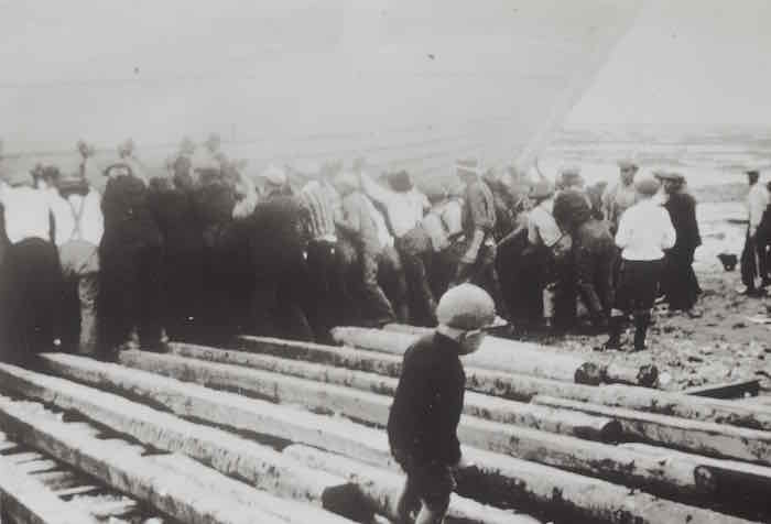 Photo ancienne en noir et blanc. Au premier blanc un jeune enfant marche seul sur des planches de bois. À l'arrière, une vingtaine d'hommes poussent une goélette vers le fleuve.