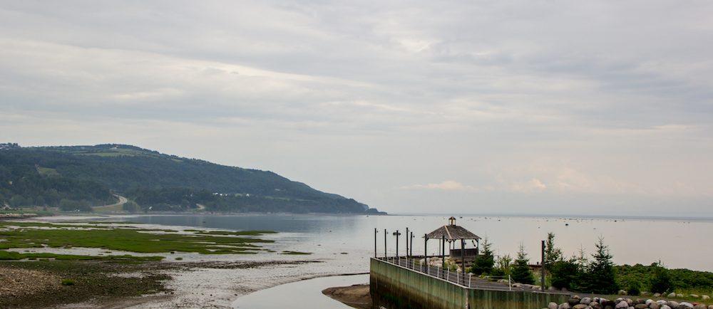 Vue sur la baie de Saint-Joseph-de-la-Rive à partir du site du Musée maritime de Charlevoix. Un quai de bois s'avance dans le fleuve au premier plan.