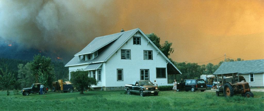 Une famille fuit leur maison. Un feu fait rage  à l'arrière plan.