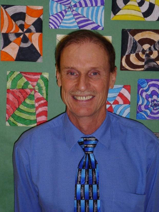 Homme vêtu d'une chemise bleue et cravate souriant à la caméra.