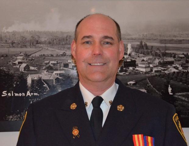Homme souriant vêtu d'un uniforme, chemise et cravate.