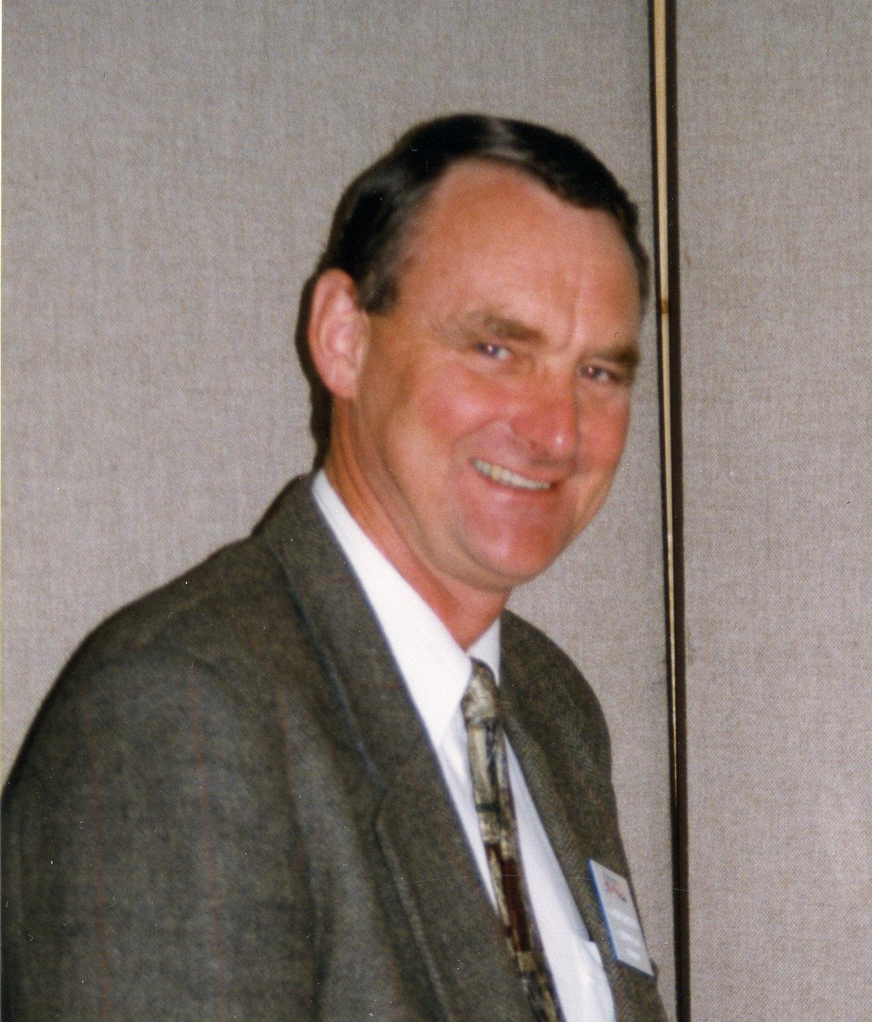 Homme souriant vêtu d'un habit et cravate.