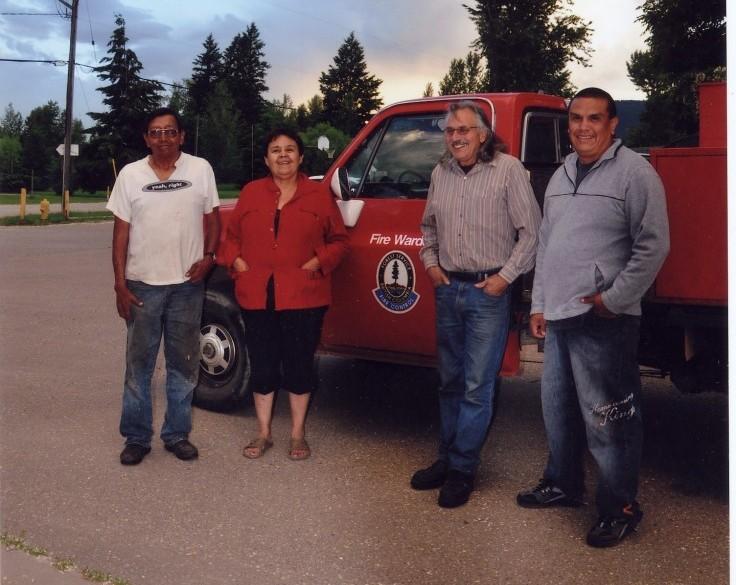 Trois hommes et une femme debout devant le camion rouge d'un officier en gestion de feu.
