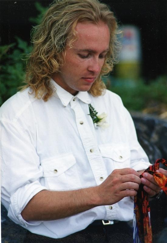 Homme en chemise blanche de style western épinglée d'une rose blanche. Tient un morceau de tissu coloré.