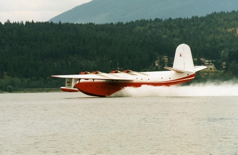 Hydravion rouge et blanc se pose sur l'eau. Colline en arrière-plan.