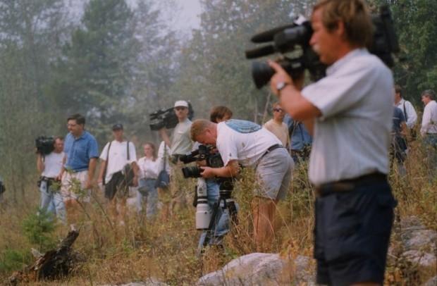 Photographe en train de filmer, debout sur le gazon.