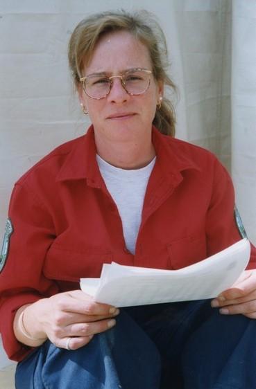 Une femme blonde assise portant lunettes regarde vers la caméra. Elle tient un papier.