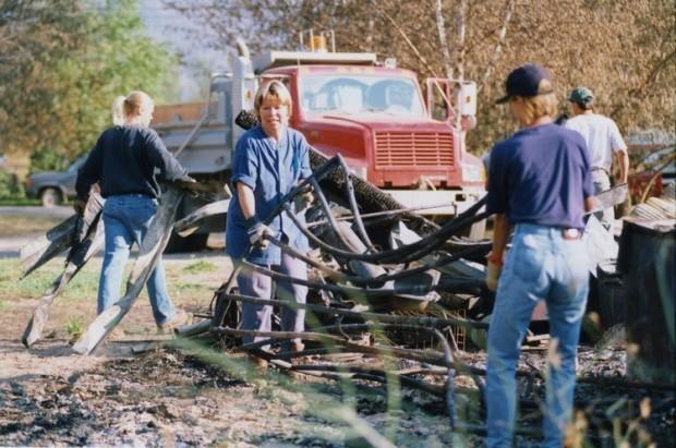 Deux femmes soulèvent du métal tordu d'une pile. Un adolescent transporte du métal vers un camion à benne.