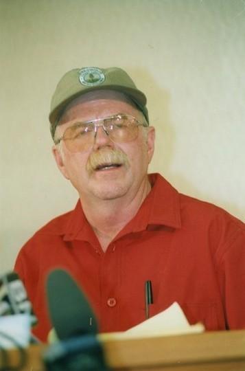 Homme coiffé d'une casquette parle dans des microphones.