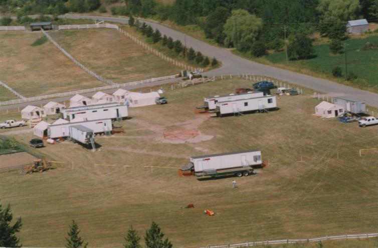 Vue aérienne de remorques, tentes et une piste d'atterrissage dans un champ.