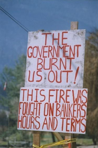 Une affiche de protestation faite à la main peinturée blanche avec lettres en rouge.