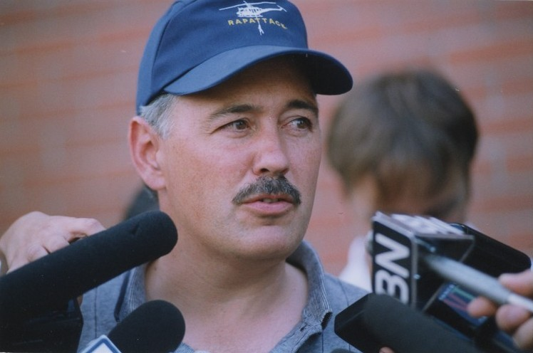Homme coiffé d'une casquette parle dans quatre microphones.