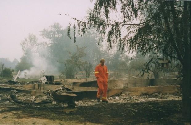 Pompier marchant dans des décombres brûlants. La fondation est tout ce qui reste.