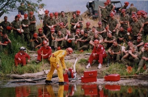 Groupe de soldats et de personnel du ministère des Forêts regardent un homme en combinaison jaune travailler avec une pompe à eau. La plupart portent des casques de sécurité. Eau au premier plan.
