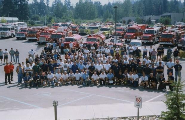 Pompiers assemblés devant des camions de pompiers et des camions-citernes pour une photo de groupe.