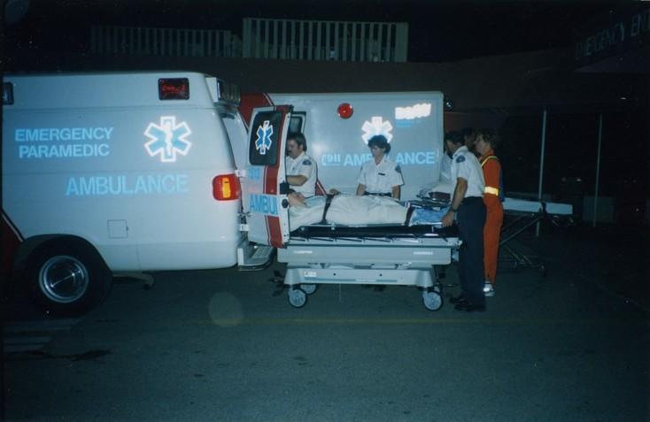 Trois ambulanciers metten un homme sur une civière dans l'ambulance. Ouvrier en uniforme orange avec bandes réfléchissantes regarde.