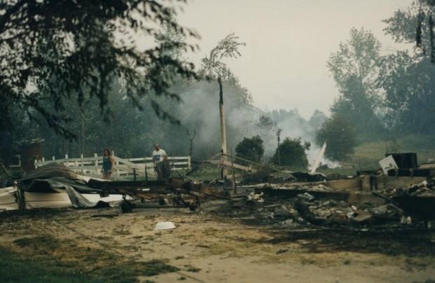 Couple marche dans une fondation, métal tordu et décombres visibles. Fumée en arrière-plan.