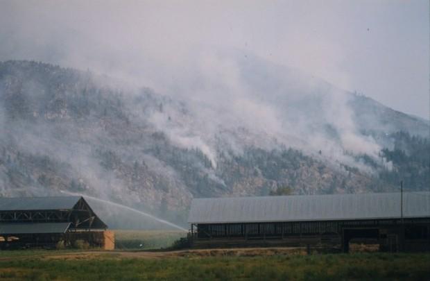 Incendie sur les collines derrière une ferme, granges devant. Eau aspergeant les champs.