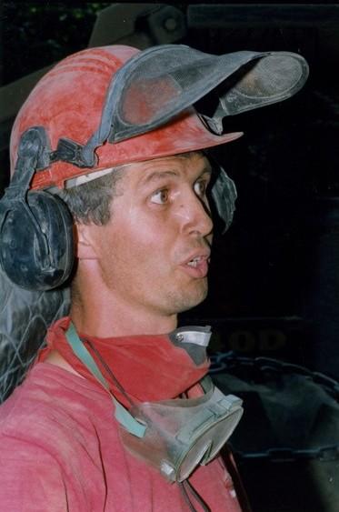 Homme en chemise rouge avec un masque et des lunettes de protection autour du cou, coiffé d'un casque de sécurité