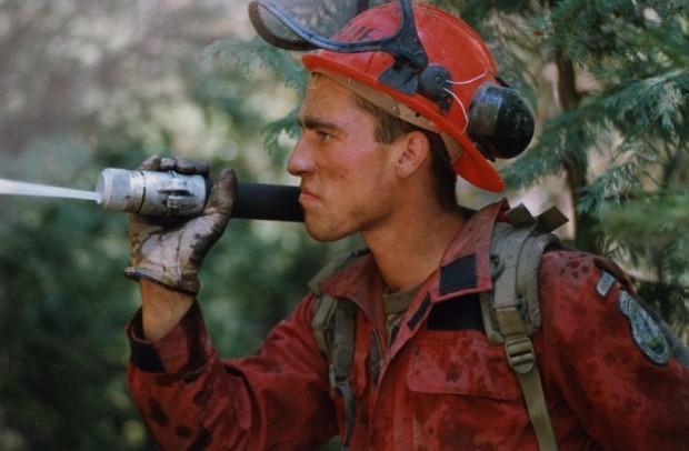 Homme en combinaison et casque de sécurité tient un boyau d'arrosage sur son épaule et arrose quelque chose hors de vue.