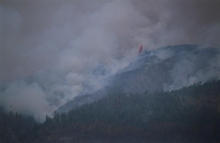 Feu et fumée dans les collines. Retardant rouge largué d'un hélicoptère.