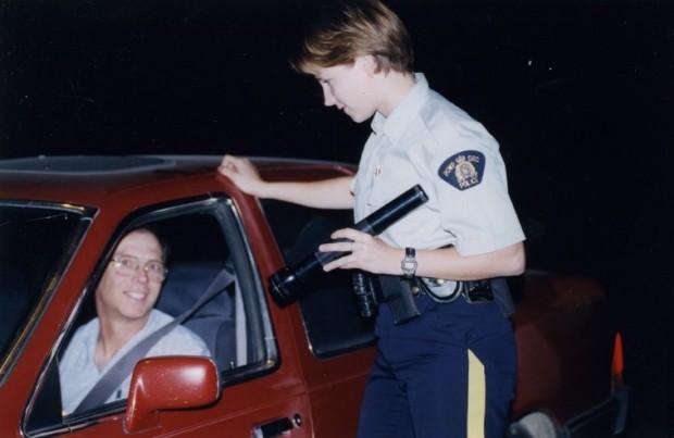 Une policière dirige une lampe de poche vers le conducteur d'une auto rouge.