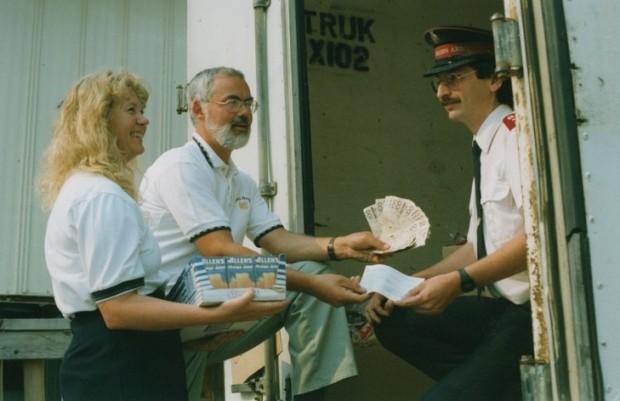 Homme et femme offrent plusieurs billets de $100., un chèque et des boîtes de jus à un officier de l'Armée du Salut.