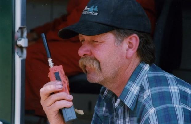 Homme vêtu d'une chemise bleue et blanche et d'une casquette bleue parle dans un radiotéléphone.
