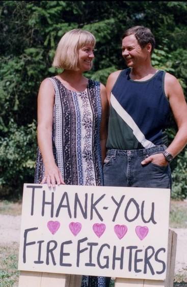 Homme et femme souriant. Elle tient une affiche disant: « Merci pompiers ».